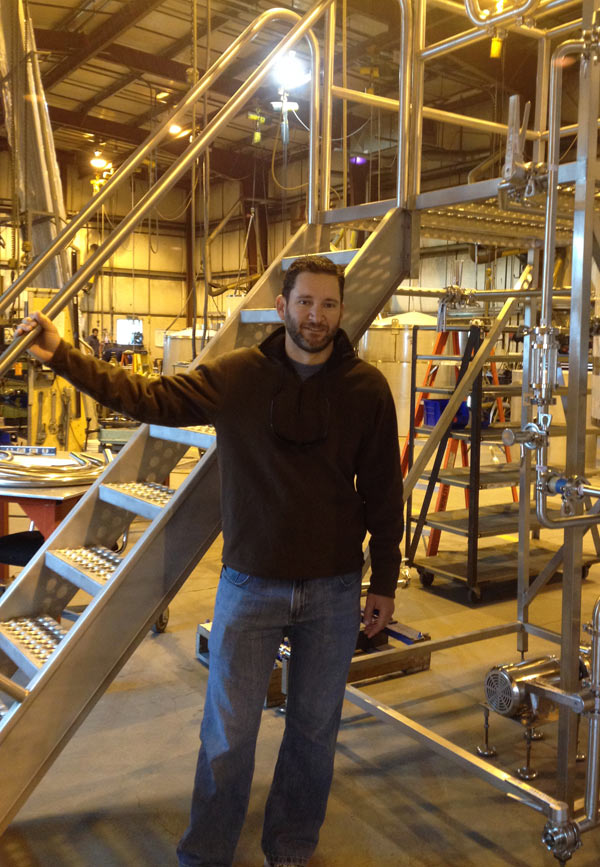 Photo of Mat Cox leaning on equipment in the brewery.